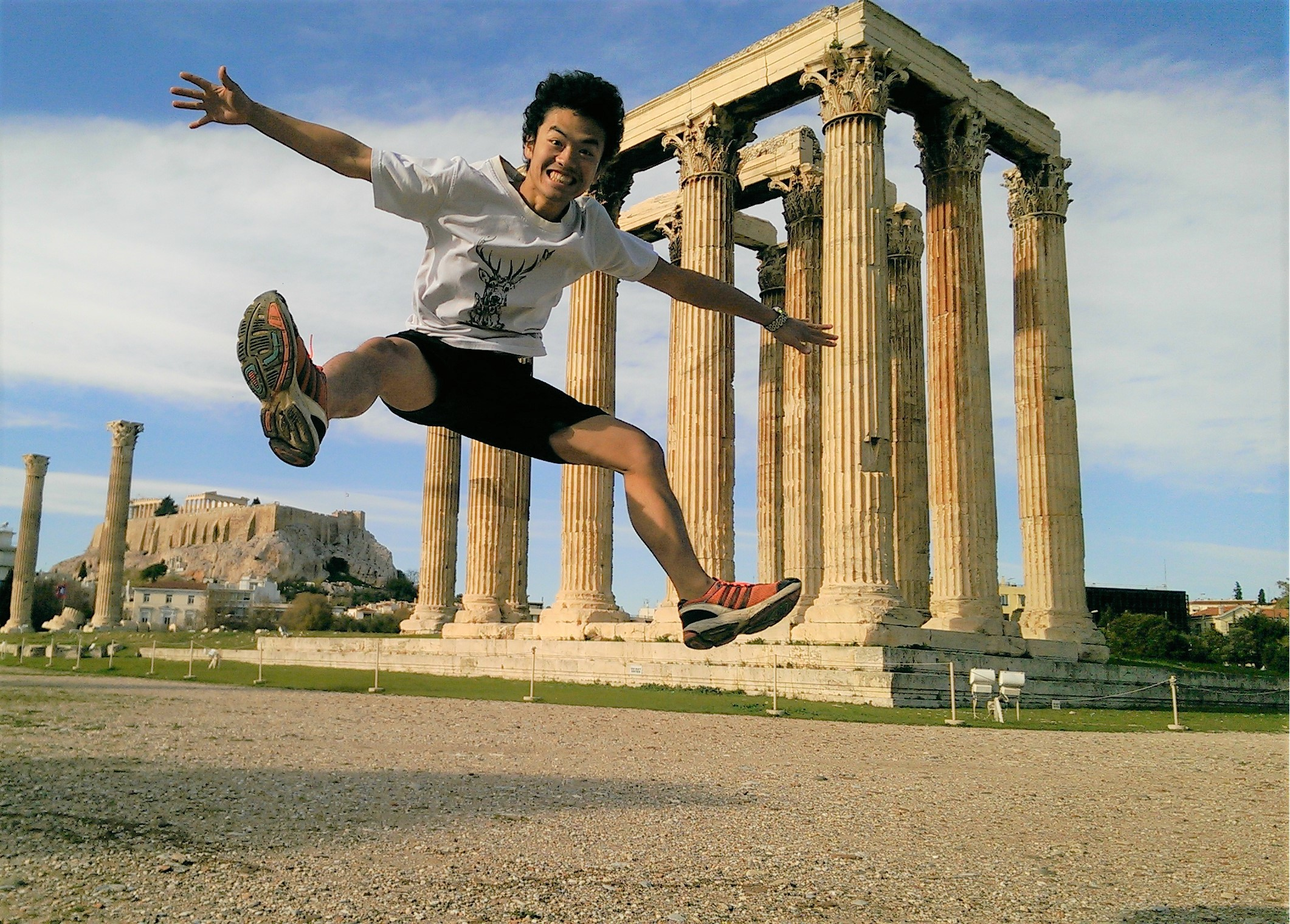 An enthusiastic student jumping in front of Greek ruins
