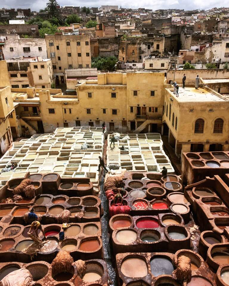 Large vats of dye being stirred on the rooftops of an old city
