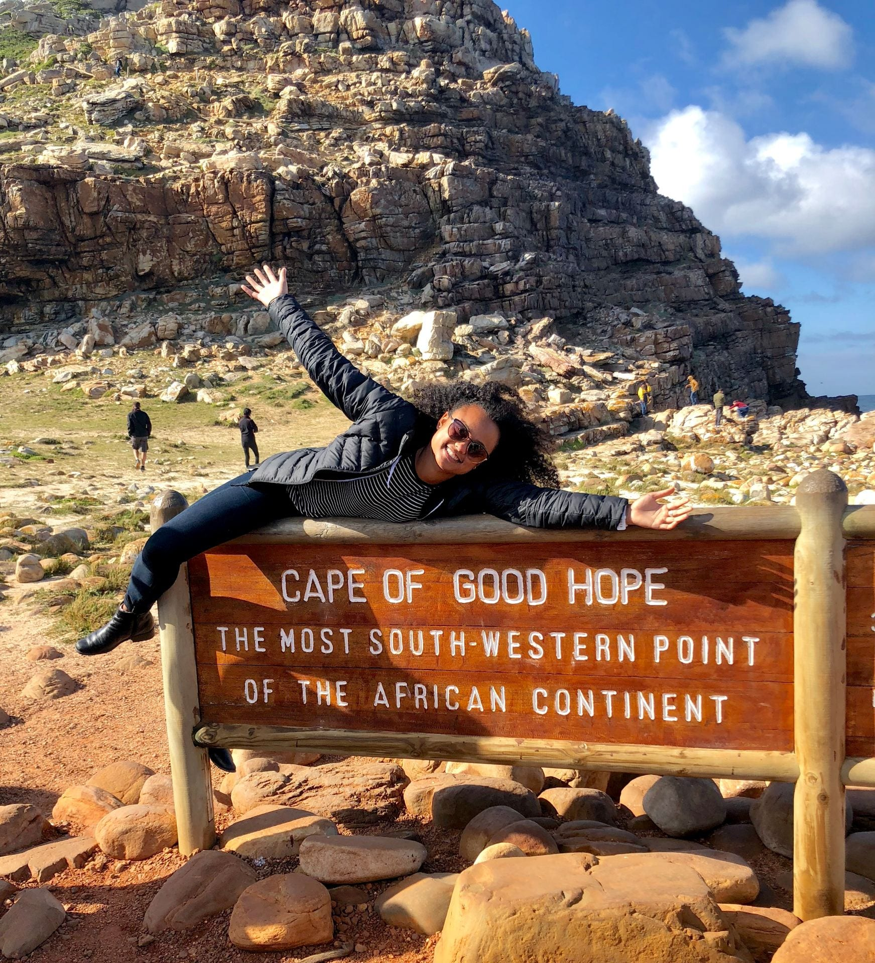 "A woman posing on a sign reading, ""Cape of Good Hope: The most south-western point of the African continent"""