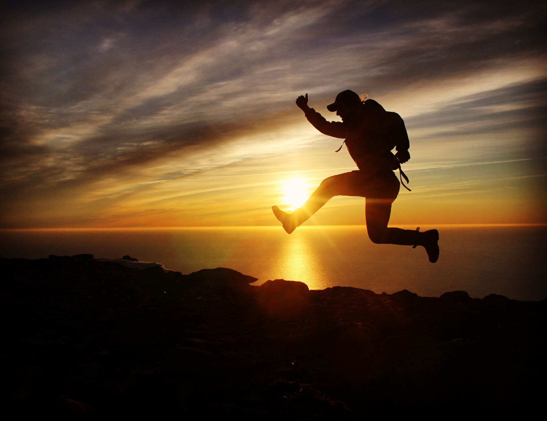A person in a hat and backpack jumping and giving a thumbs up, sillhouetted by a setting sun