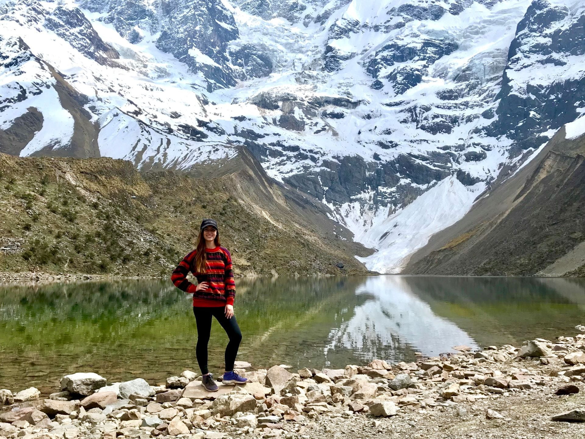 A woman posing in front of a snowy mountain, reflected in a lake