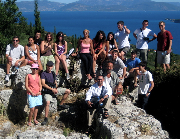group of students on a rock in Greece with water in background