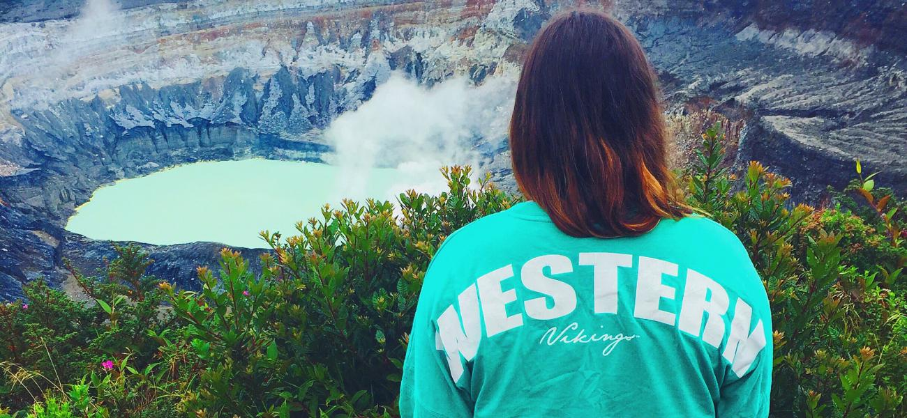 a person in a Western shirt looking out at an aquamarine lake in a valley