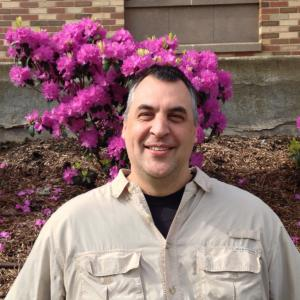 Dan Lindeman in front of a bush of flowers