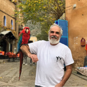 Photo of Christopher Wise with a parrot on his right arm
