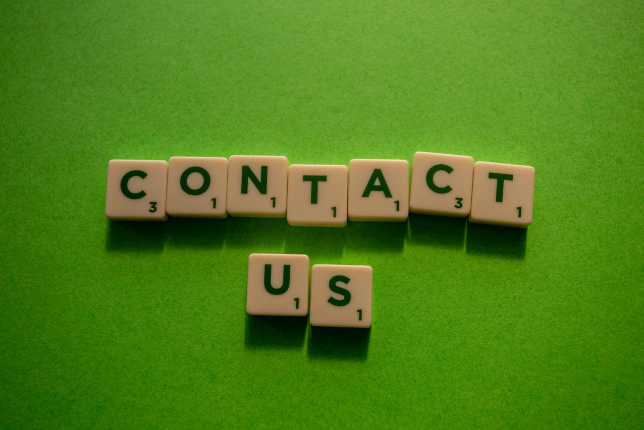 "Scrabble tiles spelling, ""Contact Us"" by Miles Burke"
