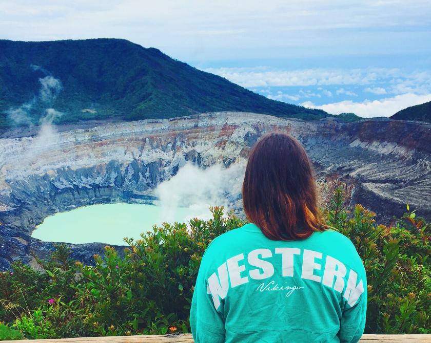 Student wearing a green WESTERN shirt looking at the Poás Volcano in Costa Rica