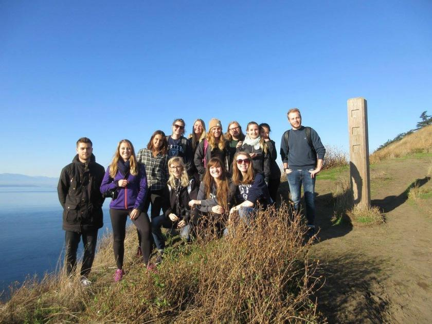 International Buddies (group of 13 students) at Ebey's Landing standing in the sunshine off the side of a trail smiling at the camera