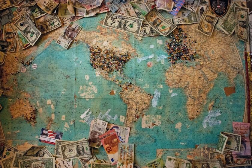 Image of a world map and money on pinned to it.